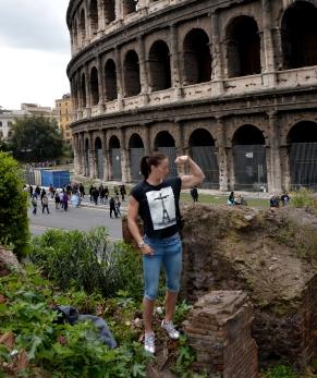 Una Gladiatrice Moderna mostra i muscoli davanti il Colosseo